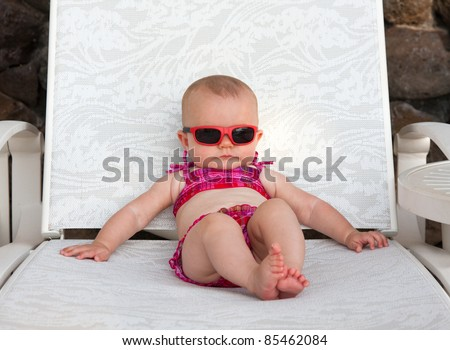 Serious baby on beach in bikini