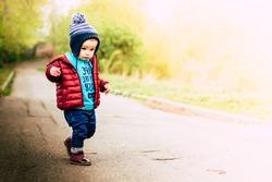 Serious baby wearing warm beanie hat, sweatshirt and jacket walking outdoors