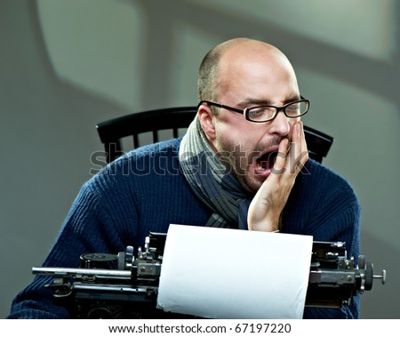 Serious bald man in scarf and glasses yawning at a typewriter - stock photo