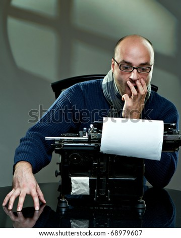 Serious bald writer in glasses. Sitting at a typewriter