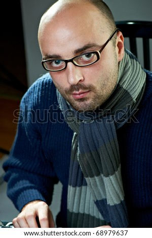 Serious bald writer in glasses. Sitting at a typewriter - stock photo