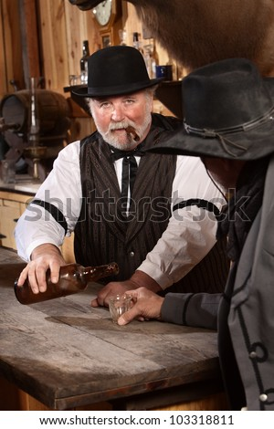 Serious bartender with cigar pours drink for customer
