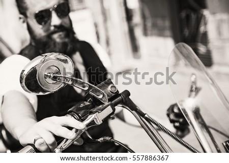 Serious Bearded Biker Man in black jacket sitting on motorbike outdoors #557886367