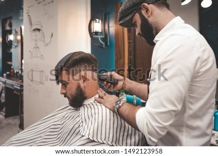 serious bearded guy doing haircut in barbershop. barbershop concept