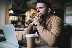 Serious bearded guy in casual wear pondering on project solution working remotely in cafe interior with disposable coffee cup, thoughtful businessman contemplating on ideas on freelance job