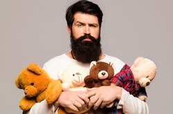 Serious bearded man hugging teddy bear. Male with plush toy. Birthday, anniversary and holiday celebration.