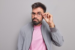 Serious bearded man keeps hand on rim of spectacles has attentive gaze directly at camera has surprised expression wears jacket isolated over grey background listens something. Monochrome shot