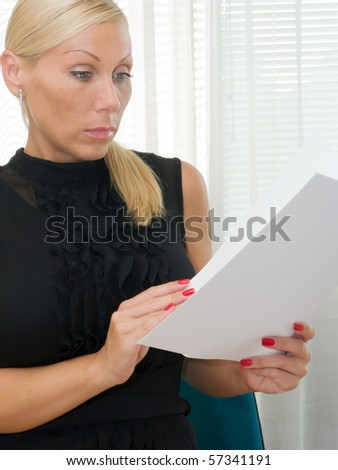 Serious beautiful businesswoman reading a document