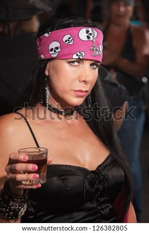 Serious beautiful woman in motorcycle gang outfit in bar
