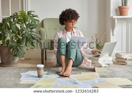 Serious black lady with Afro haircut, makes research work, checks data on laptop computer, holds documents, poses at floor in fashionable clothes, surrounded with pile of books. Student studies indoor