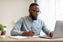 Serious Black Man Writing Business Report At Laptop Or Filling Tax Form At Workplace Sitting In Modern Office. Paperwork, Entrepreneurship Occupation And Career Concept