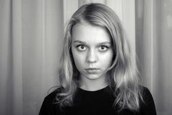 Serious blond Caucasian girl, monochrome studio portrait