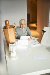 Serious blonde elderly person with a pair of spectacles in her hand scrutinizing a document