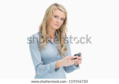 Serious blonde woman a while texting on her smartphone