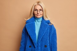 Serious blonde woman in blue fur coat looks with charming expression directly at camera satisfied after going shopping and buying fashionable winter outerwear isolated over brown background.