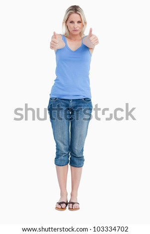Serious blonde woman showing her thumbs up against a white background
