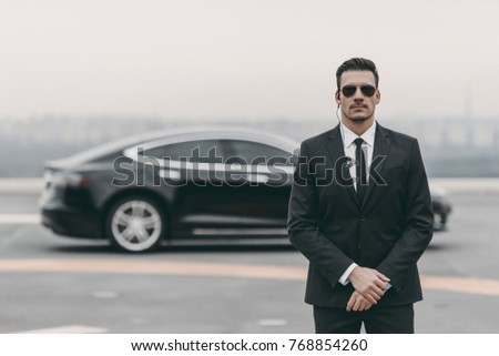 serious bodyguard standing with sunglasses and security earpiece on helipad  Сток-фото ©