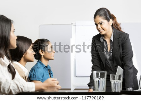 Serious boss talking with her team during a meeting. Indian business woman.