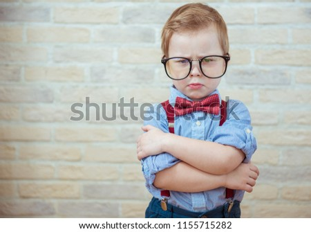 Serious boy standing with in big glasses. The concept of the evil boss Foto stock ©