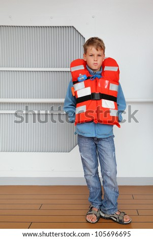 Serious boy wearing in orange life jacket stands at deck of ship.