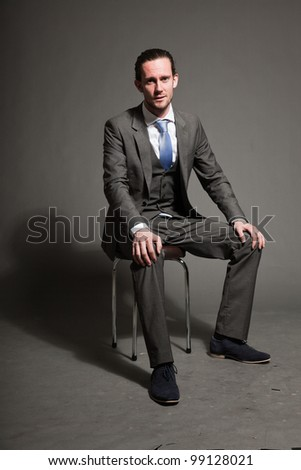 Serious business man brown long hair with expressive face wearing grey suit and blue tie sitting on chair. Isolated on grey background.