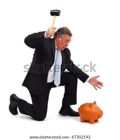 Serious business man raising hammer to break the piggy bank - stock photo