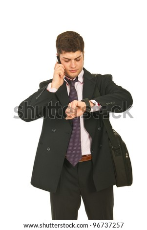 Serious business man speaking by phone mobile and checking time isolated on white background