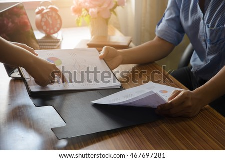 Serious business people discussion about  year planner, business man holding a smart phone and business woman pointing at something on paper,notebook on wood table #467697281