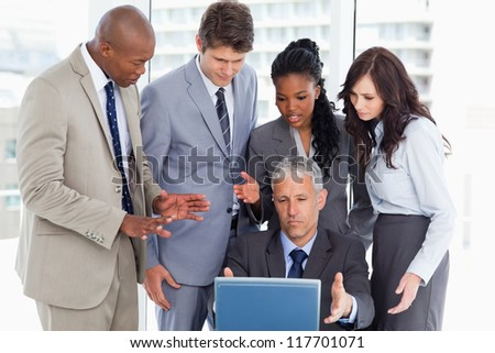 Serious business team talking in front of a computer