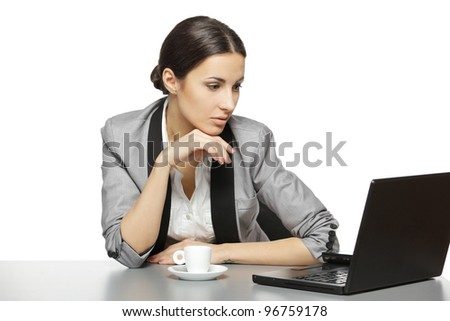 Serious business woman reading at laptop screen sitting at her work desk, isolated on white background