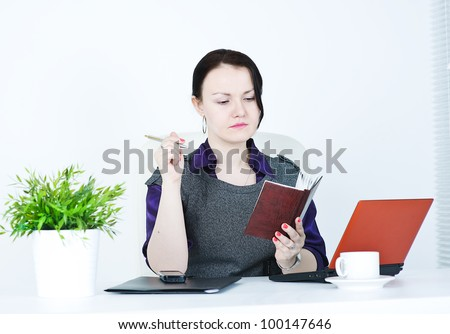 Serious business woman with notebook and pen