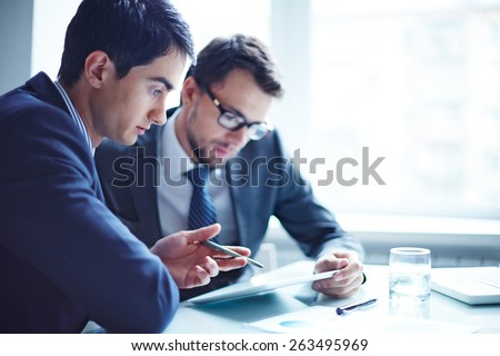Serious businessman explaining data to his colleague at meeting - Shutterstock ID 263495969