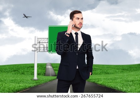Serious businessman hand in pocket phoning against road leading out to the horizon