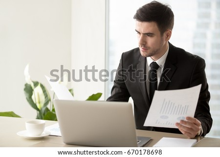 Serious businessman holding financial report, analyzing project stats, studying advertising campaign effectiveness, looking at work results and company growth, reviewing exchange trading statistics