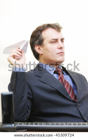 Serious businessman in formal wear aiming paper plane