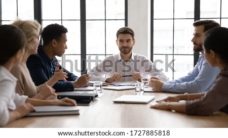 Serious businessman listening mature employee about project sit at table in boardroom at company meeting. Confident leader discuss business strategy with diverse colleagues in conversation. Сток-фото ©