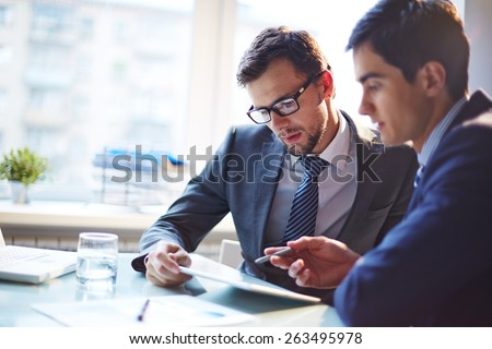 Serious businessman listening to his colleague explanations at meeting - Shutterstock ID 263495978