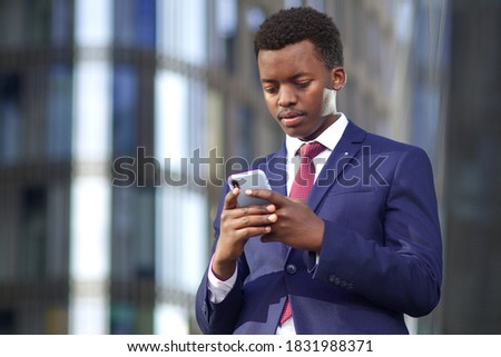Serious businessman looking at his cell mobile phone, typing a message. Black African Afro American man in suit outdoors with smartphone.  Stock photo ©
