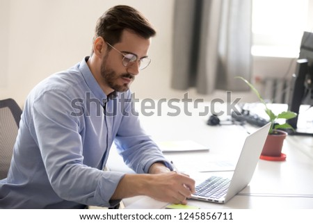 Serious businessman making notes, working with paper documents, writing report at workplace, focused employee doing economic research with laptop, male student studying online learning course