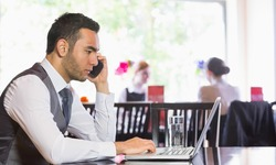 Serious businessman man calling on phone using laptop in a restaurant