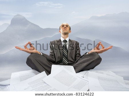 Serious businessman meditating with raised hands in mountains