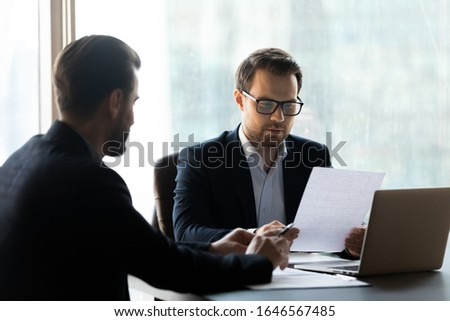 Serious businessman reading cv new job candidate and using laptop. Handsome young leader listening terms of transaction from partner. Difficult business decision about make corporate deal.