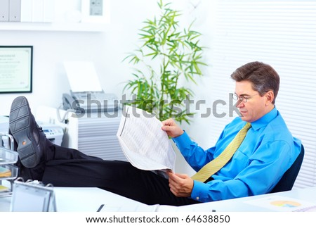 Serious businessman reading newspaper in the office - stock photo