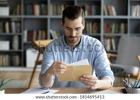 Serious businessman sit at workplace office desk holding envelope take out letter feels interested read business news, got invitation, learns bank statement information. Postal correspondence concept