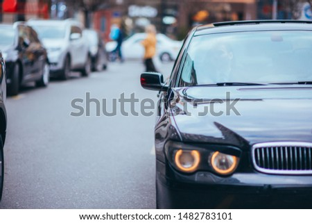 Serious businessman sitting at the front seat in his limo on a busy city street.