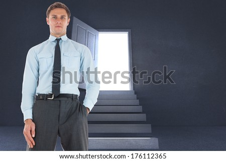 Serious businessman standing with hand in pocket against steps leading to open door showing light
