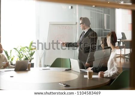 Serious businessman talking giving presentation on flipchart, explaining new company strategy to colleagues during briefing, male worker training associates on reaching business goals at meeting #1104583469