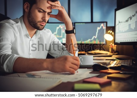 Serious businessman thinking hard of problem solution working late in office with computers documents, thoughtful trader focused on stock trading data analysis, analyzing forecasting financial rates