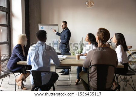Serious businessman training speaker coach wear suit give presentation at company meeting, confident male leader executive drawing on flip chart teaching business team at corporate office workshop