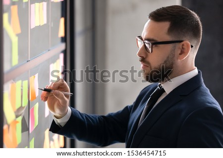 Serious businessman wear suit writing business ideas or tasks list on post it sticky notes on scrum board, focused male ceo planning corporate project strategy organize managing work on glass wall